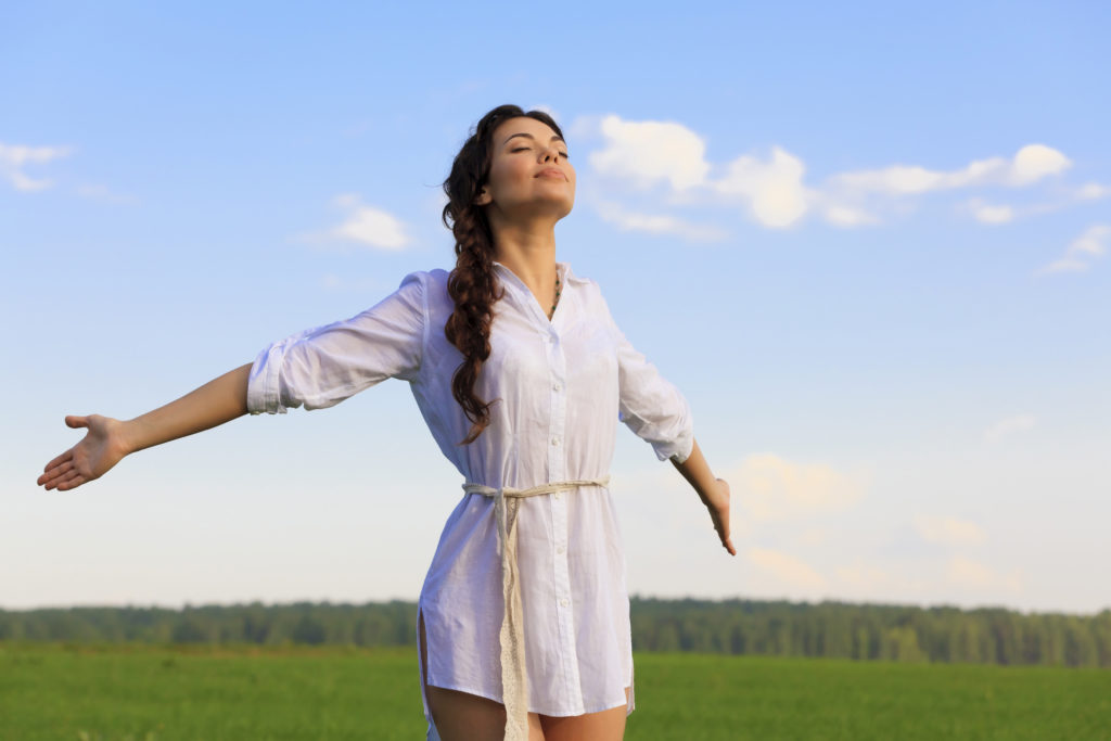 a woman stands in a field looking peace and refreshed